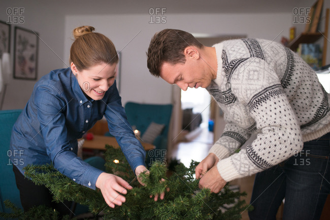 Couple assembling artificial Christmas tree