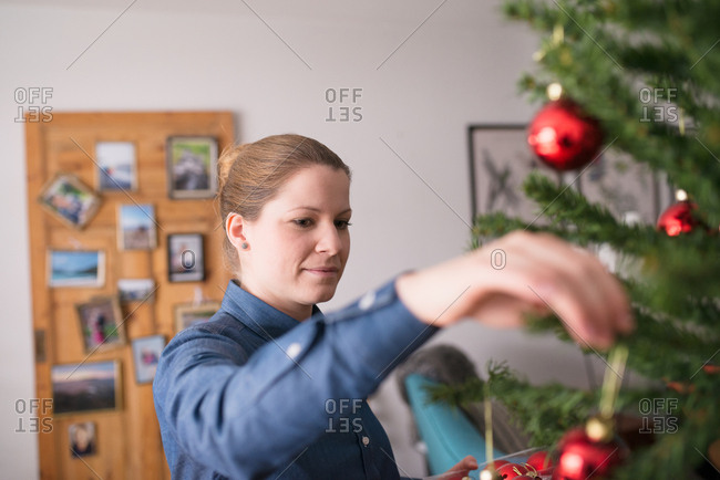 Woman hanging red ornaments on a Christmas tree
