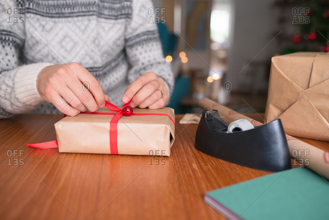 Man wrapping gift with red ribbon