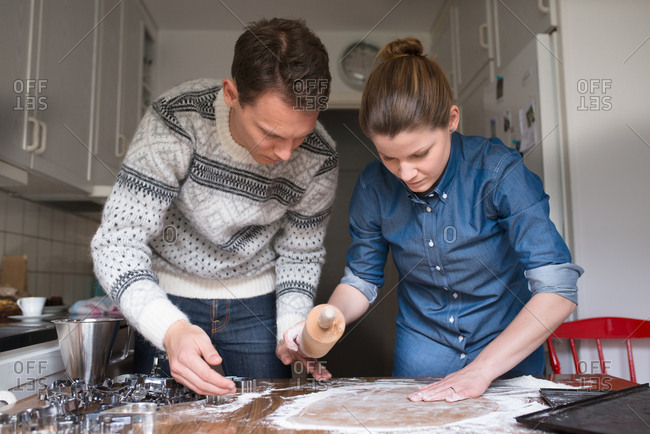 Couple rolling out dough for cookies