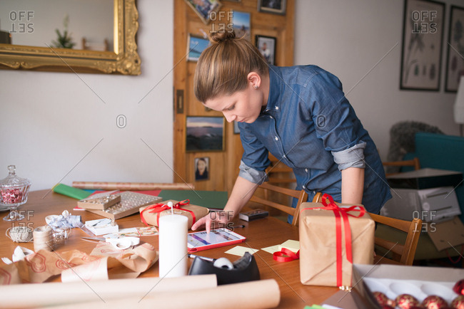 Woman using tablet while wrapping Christmas gifts