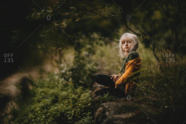Blonde girl sitting in rural setting