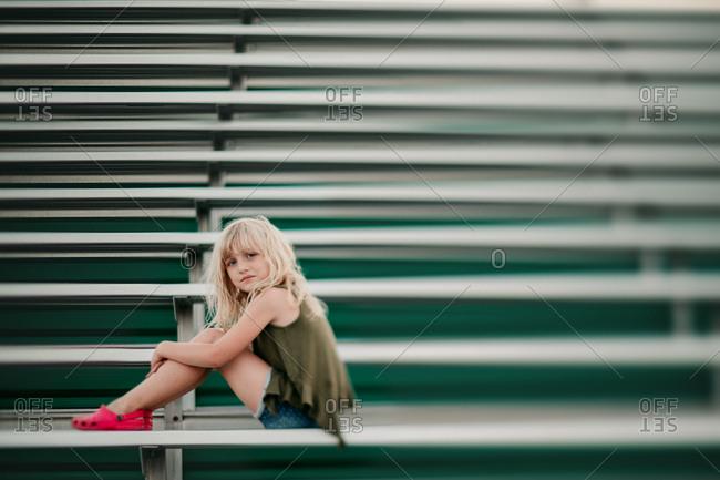 Blonde girl sitting on bleachers