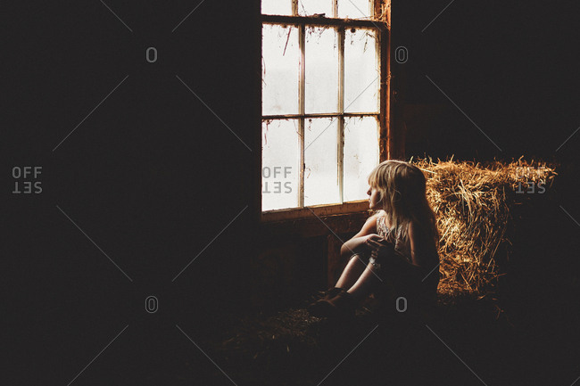 Young girl sitting in barn on bale of hay