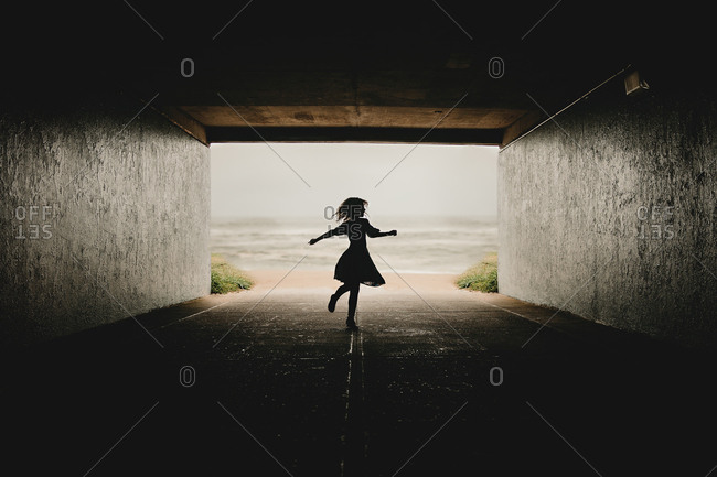 Silhouette of child dancing under bridge by the ocean