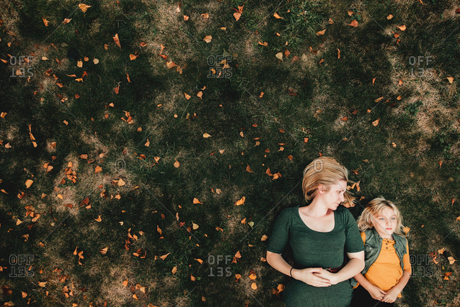 Mother and daughter lying on ground with fallen leaves