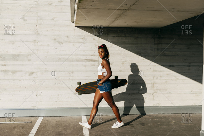 Side of young black girl in summer outfit holding long board and walking in sunlight at street.