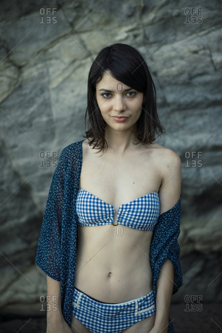Young confident woman posing near the stones