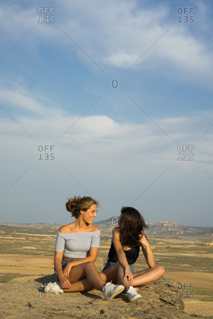 Excited women lying on cliff