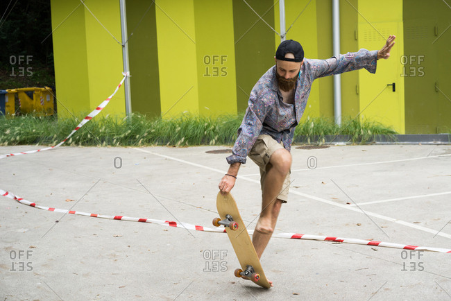 Handsome bearded man performing trick on skateboard riding on parking lot.