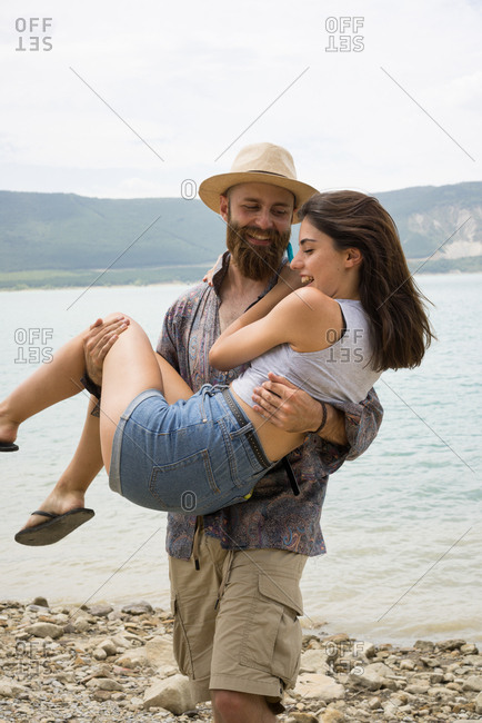 Smiling man carrying cheerful girlfriend on hands at the water on the beach.