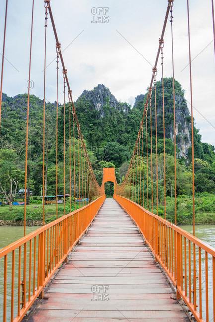 Perspective of metal hanging bridge crossing river in tropical woods.