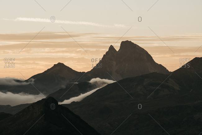 Landscape of bare rocky mountains with clouds among peaks on background of sky,