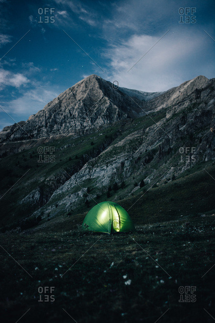 Small green tent with light burning inside on background of mountains in evening time.