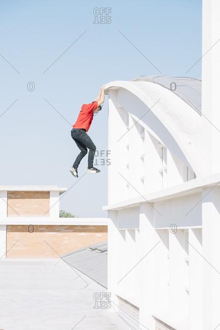 Side view of tracer man hanging on roof while doing parkour in city.