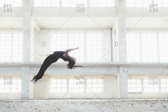 Sportswoman doing flip in urban building