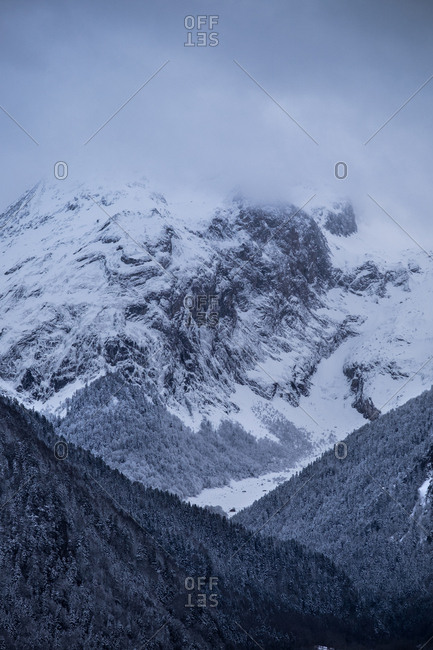Horizontal outdoors shot of snowy winter mountain with forest covered with mist.