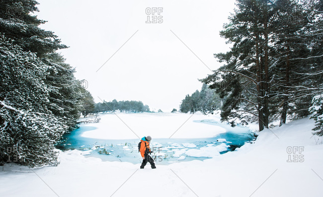 Side view of traveler man walking on forest at frozen lake in winter.