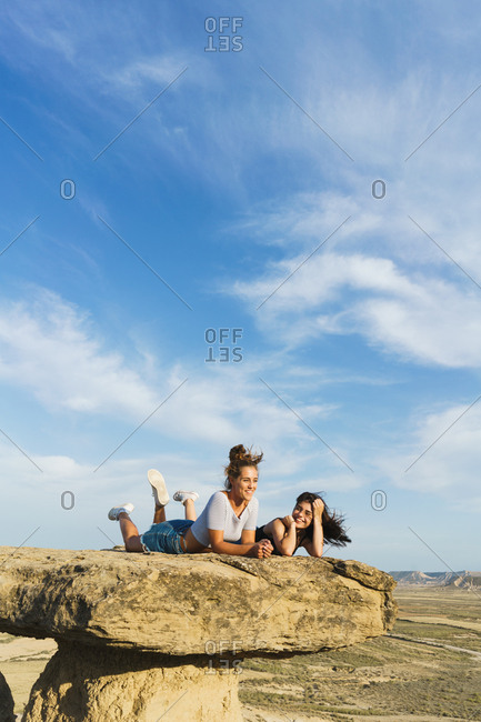 Pretty women smiling while lying on the top of the cliff.
