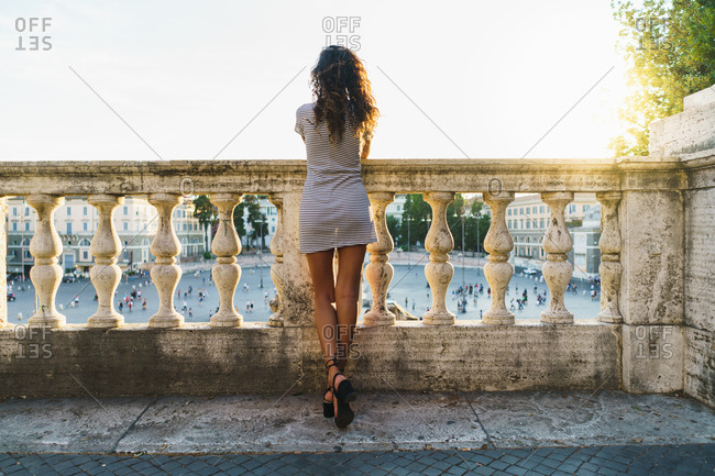 Back view of stylish fit girl standing near old stone fence in sunlight looking away.