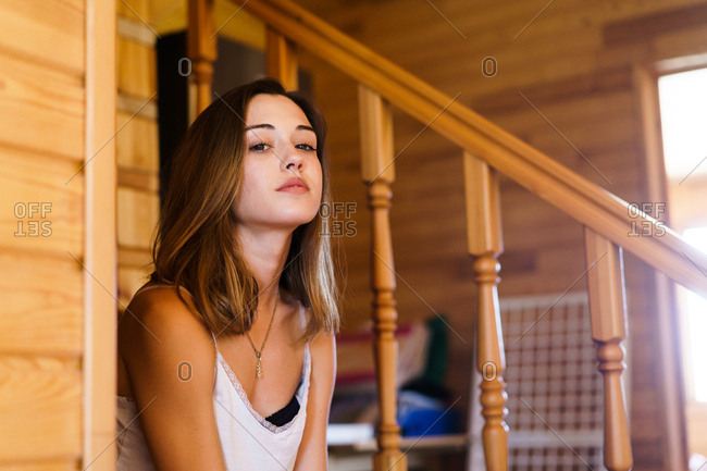 Young woman in pajamas posing near the stairs