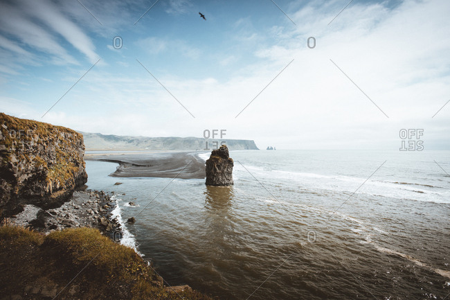 Rocky shoreline with cliffs and ocean washing coast under blue sky.