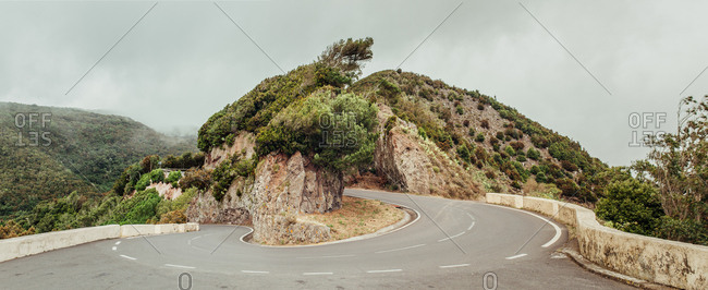 Paved road making twist in mountains in gloomy day.