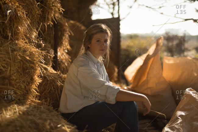 Portrait of confident young woman sitting on hay bales