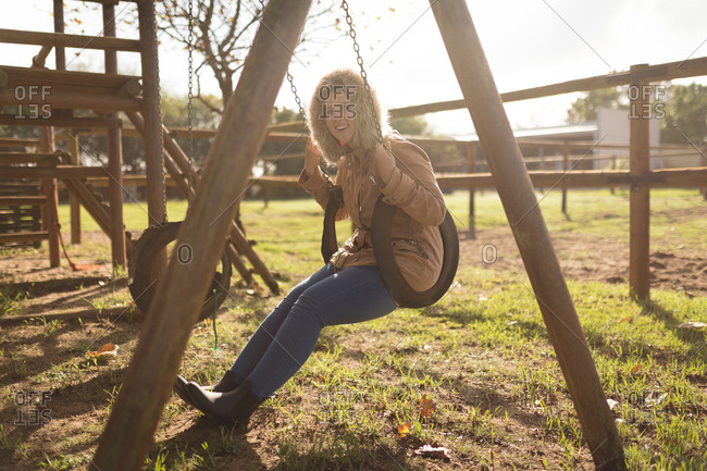 Portrait of happy woman wearing winter coat swinging in playground