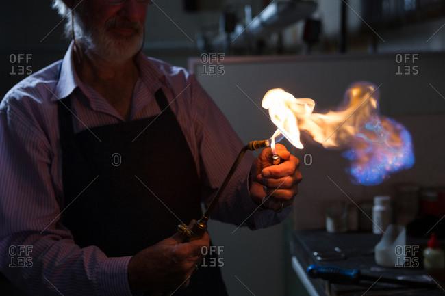 Goldsmith using welding torch in workshop