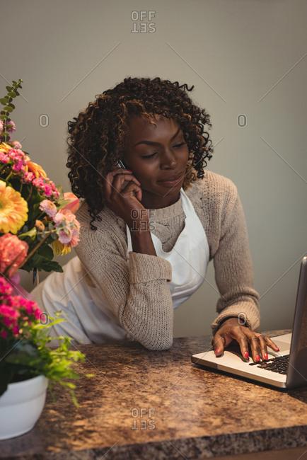 Female florist taking order on laptop