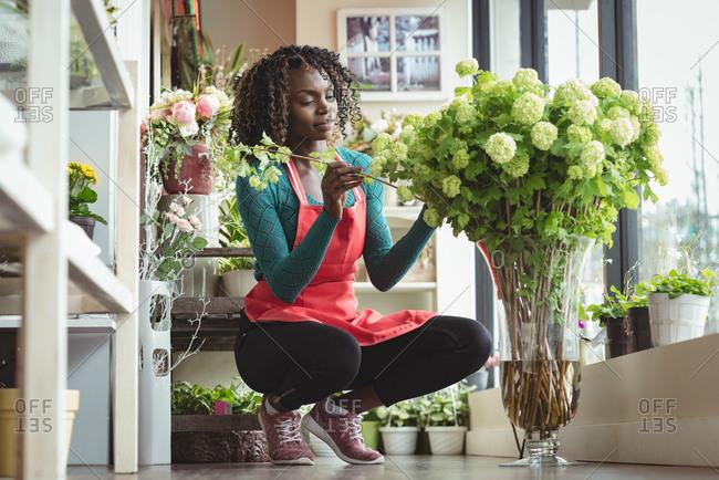 Female florist arranging flowers on flowerpot