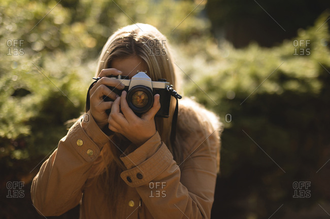 Young woman wearing winter coat photographing with camera