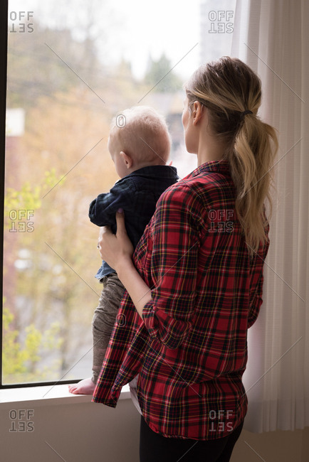 Side view of young woman with son standing by window