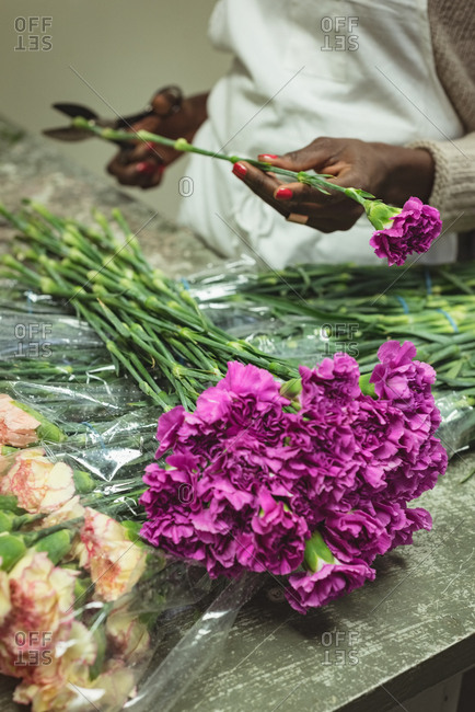 Female florist preparing bouquet of flower at his flower shop