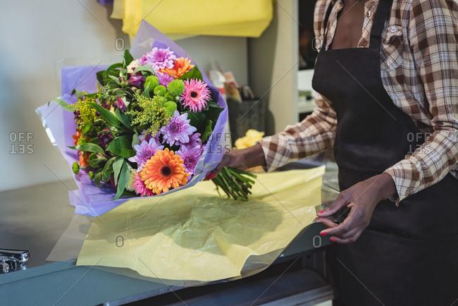 Female florist packing a flower bouquet