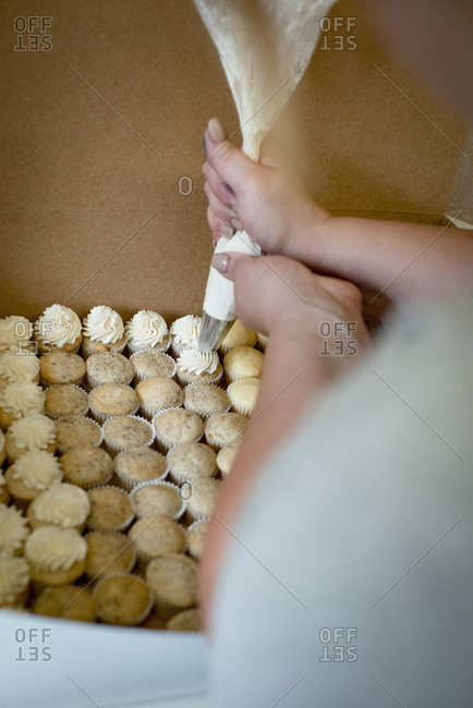 Woman putting whipped cream on cupcakes