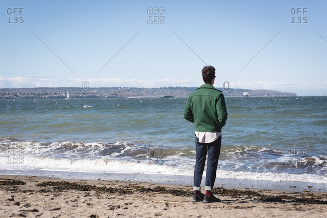 Man standing on sandy beach on sunny day
