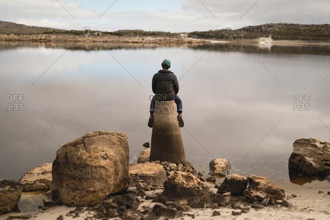 Man sitting on rock near lakeside