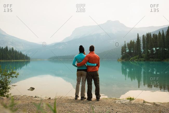Hiker couple hugging near the lake