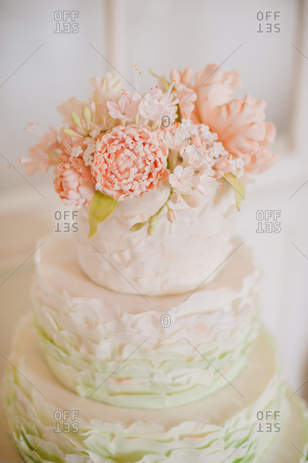 Three tiered wedding cake topped with pink flowers