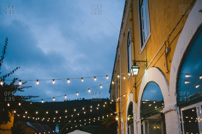 String lights illuminated at dusk during an outdoor wedding