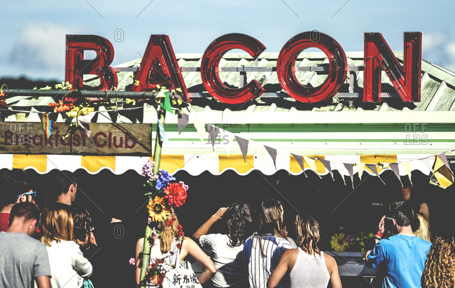 People waiting in line at Bacon food stand