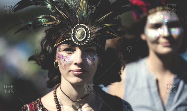 Young women at a concert wearing feather headdresses