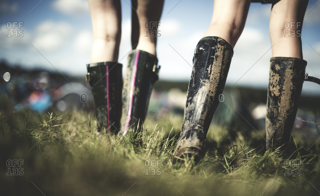Mud covered boots walking through grassy field