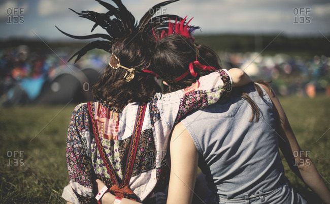 Two women at a concert wearing feather headdresses from behind