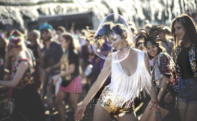 Young women at a music festival dancing with bubbles
