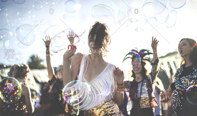 Festival goers dancing around bubbles at a concert