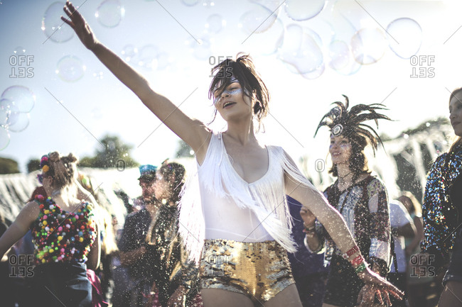 Festival goers dancing with bubbles at a concert