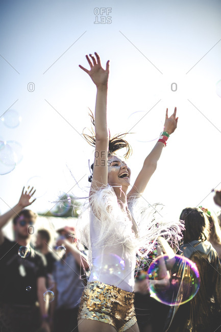 Excited woman at a music festival dancing with bubbles